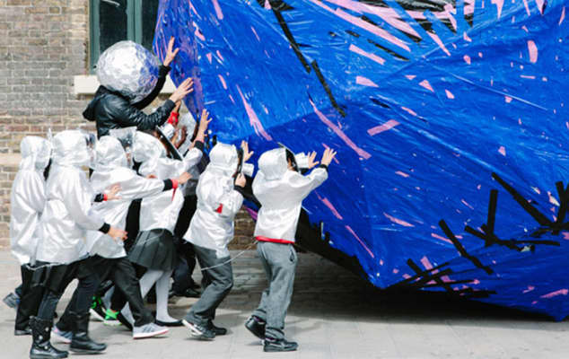 Image of a group of children pushing a giant paper sculpture through Granary Square.