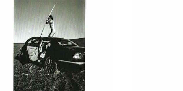 Black and white photographic image by Jiayi Chen, showing a naked figure standing on top of a car, firing a bow and arrow towards the viewer.