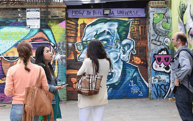 Students looking at graffiti on a tour in East London