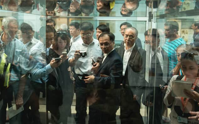 Image of museum visitors looking into a glass case.