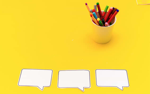 Service Design courses at London College of Communications - Image of yellow background with empty caption bubbles and colouring pencils in a cup