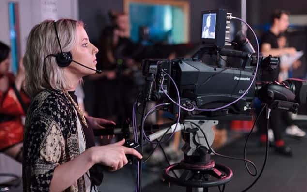 A student operating a studio film camera