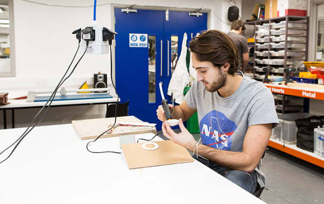 A student at a workstation, using a glue-gun in the Prototype and Code lab at London College of Communication.