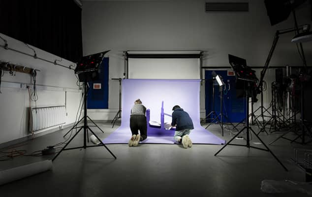 Photograph of students kneeling on the floor in a photography studio, with two specialist lights.
