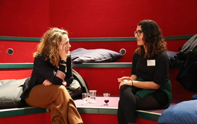 Photograph of an Industry Mentoring Scheme event at London College of Communication. Mentors and mentees having a discussion in a red seating space.