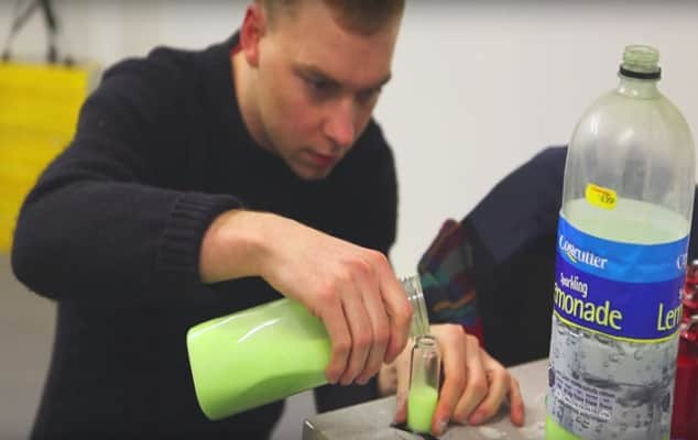 Man pouring luminous green liquid into a bottle