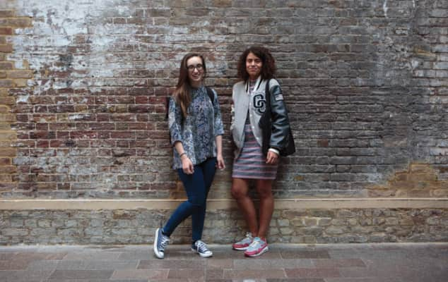 Two students standing against a wall