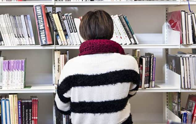 Student browsing shelves at London College of Fashion Library, by Ana Escobar, 2013