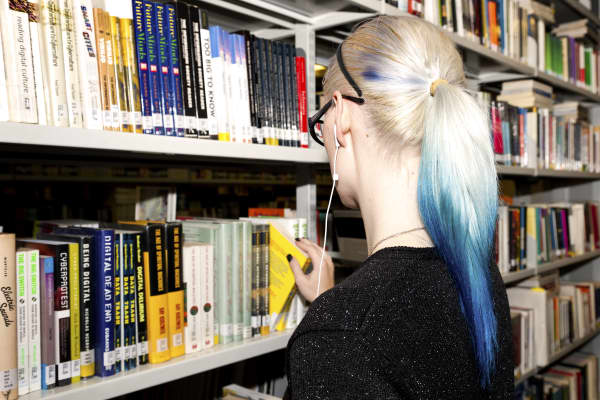 Student browsing shelves at LCC library, University of the Arts London