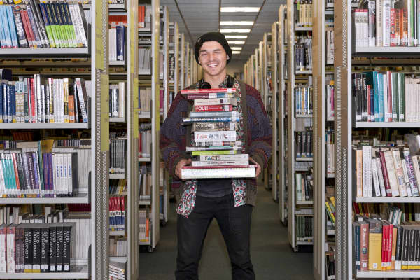Student holding stack of books at LCC library, University of the Arts London