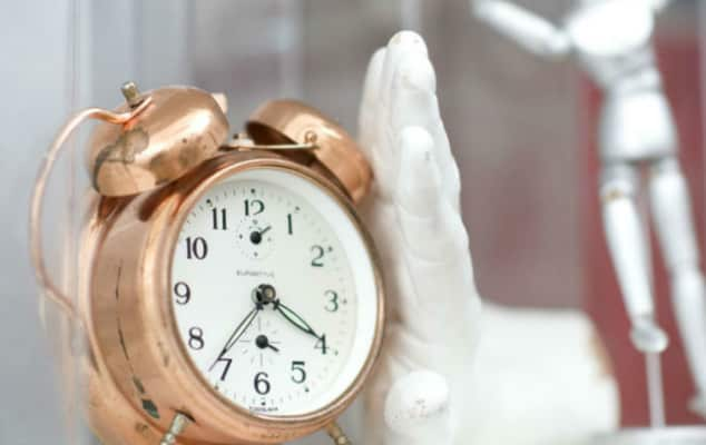 A display showing a golden clock and a hand sculpture