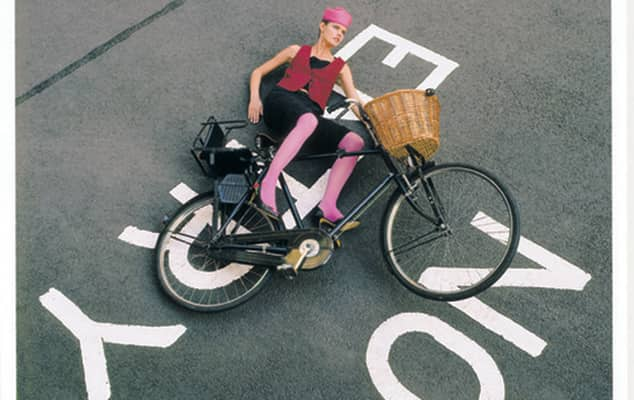 Fashion image of woman in pink tights and hat falling off bicycle on no entry sign