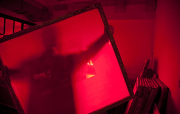 Image of person lifting a printing screen in red-lit room