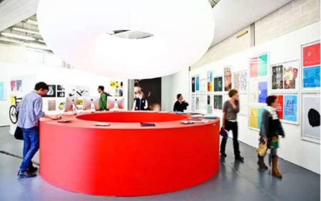 People looking at leaflets on top of large red desk and viewing artwork in exhibition space
