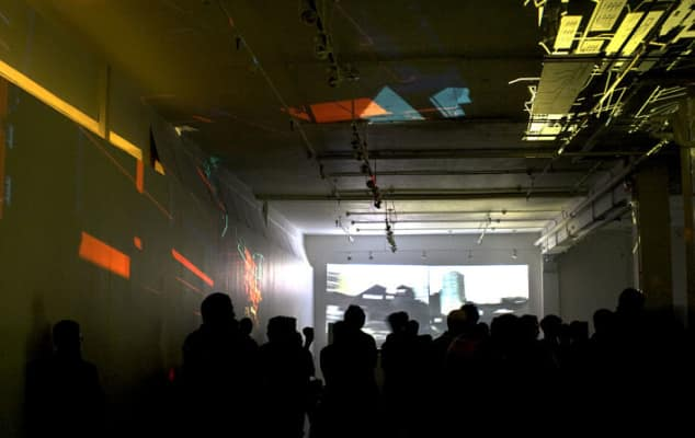 Image of crowd in a dark room watching projected images