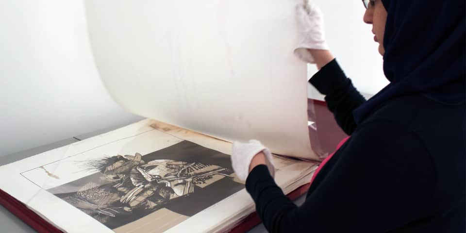 Student turning pages of large art book