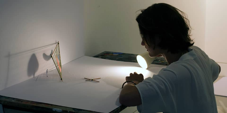 Student using a desk lamp to light a 3D model.