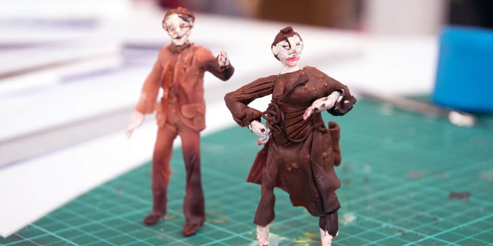 Two figures in costume created during a theatre design short course.