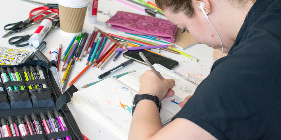 Student working on a design idea in her sketchbook during Graphic Design - Creative Process.