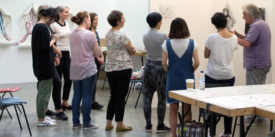 Students in discussion with the tutor, during a curating course.
