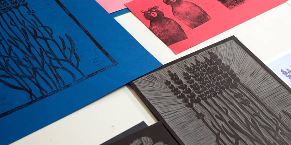 Lino prints on a desk that have been scanned to make composite illustrations.