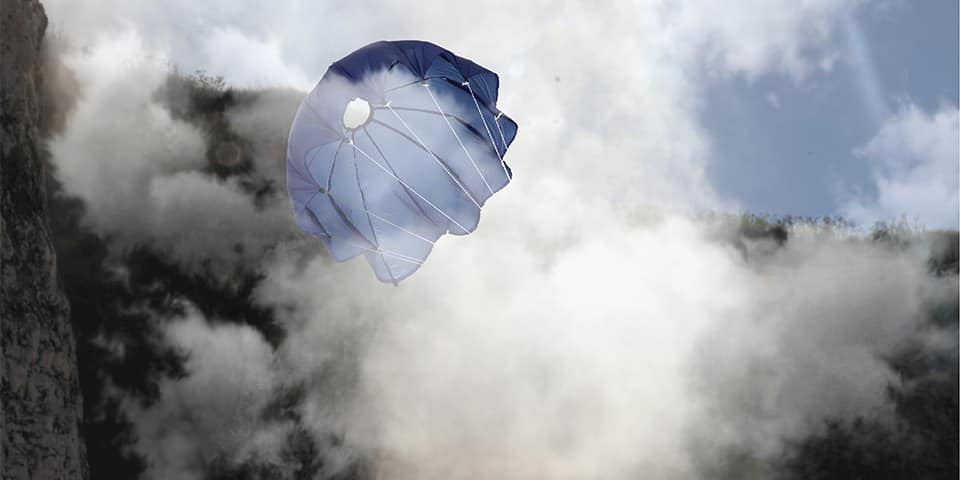 A hot air balloon style kite flying through clouds.