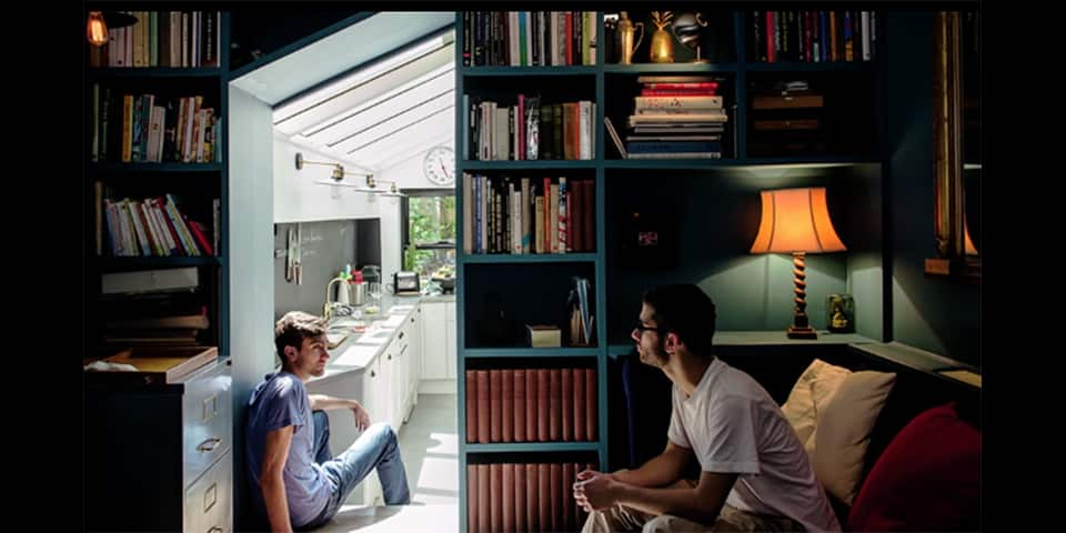 Photography by Chiara Bellamoli, showing to men sitting within a kitchen/living-room space. One man sits on a sofa, another sits on steps into a kitchen, he is bathed in sunlight.