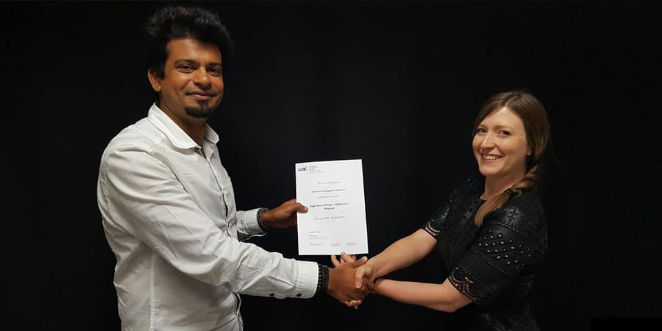 Bespoke training courses for professional development in the creative industries at London College of Communication - Picture of tutor and student. Tutor awarding student with a certificate and shaking his hand to congratulate him.