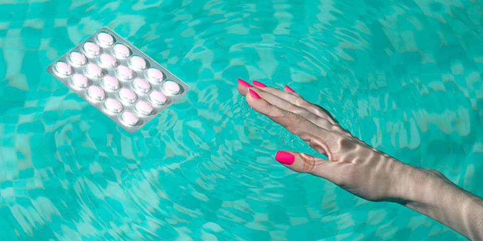 Photograph: Manicured hand in a pool reaching for some pills.