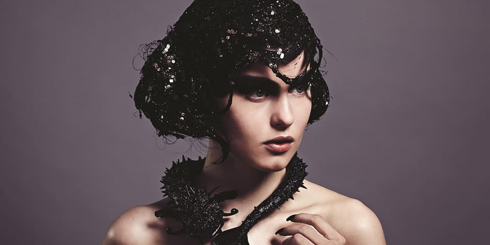 Model wearing black sequin headpiece and necklace.