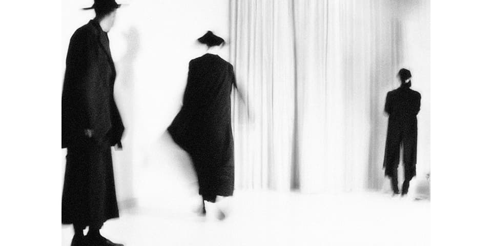 Out of focus shot of three models wearing black coats and hats in front of a white curtain