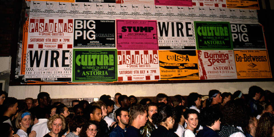 Photo of women queuing against a wall covered in club night posters, called The Trip queue, London. c.1988. Photographer Dave Swindells. Image courtesy of Dave Swindells.