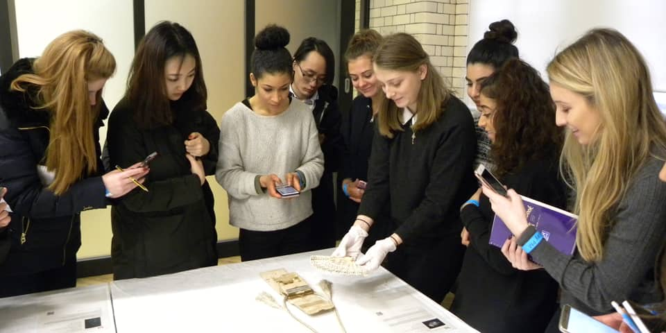 Students huddle around an archive table with some Victorian accessories on display