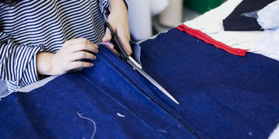 Pattern Cutting and Sewing Techniques: student cuts fabric in class