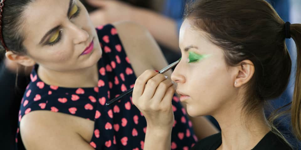 Student applying makeup to model, on fashion and editorial makeup course