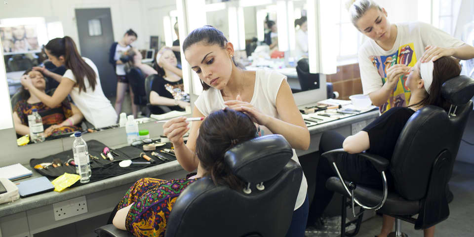 Students applying makeup to models, on fashion and editorial makeup course