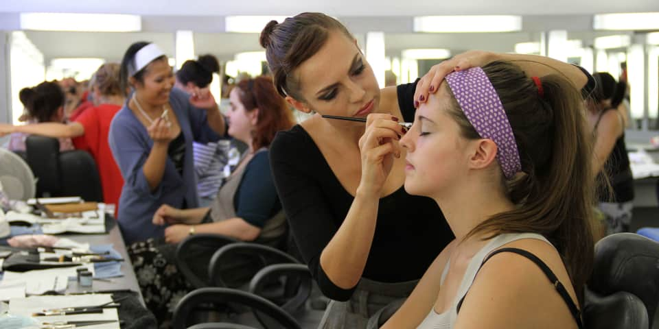 Student applying makeup to model.