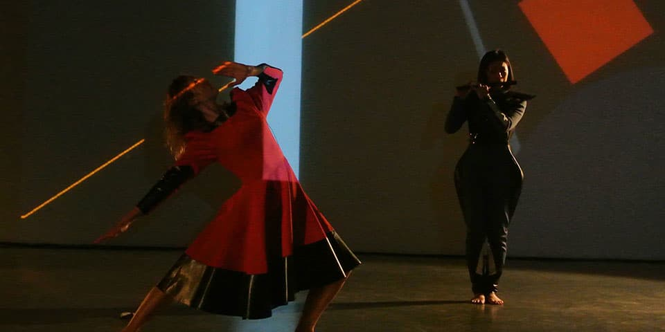 For the Time Being, Interaktionslabor X (2013) Michèle Danjoux. Vanessa Michielon in Red Micro Dress with 'Futurian' Emi Watanabe in Background on Flute Wearing Sounding Chest Plate, Act II. (photo © Michèle Danjoux). Original has been modified.