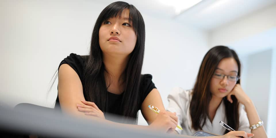 Two students at a desk in a classroom at London College of Fashion