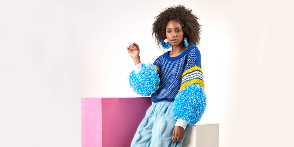 Model in bright knits and earrings.