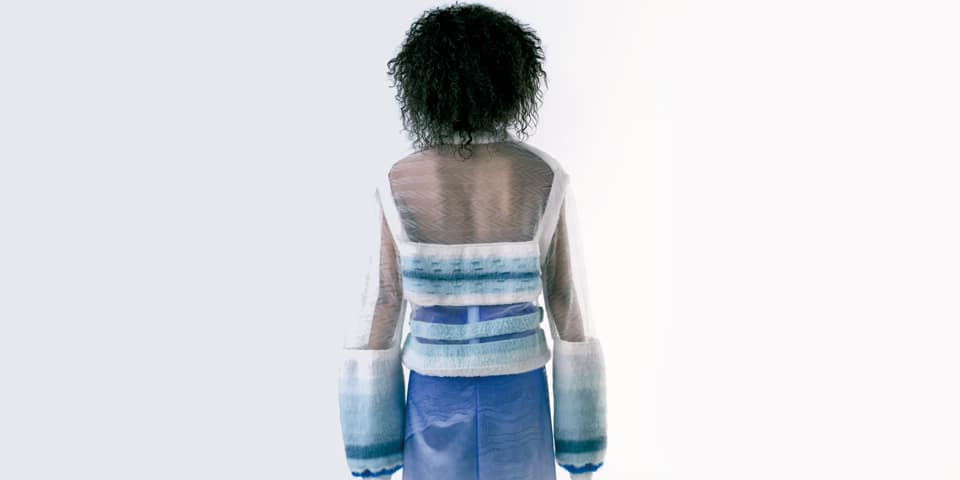 Model's back wearing semi transparent knit.