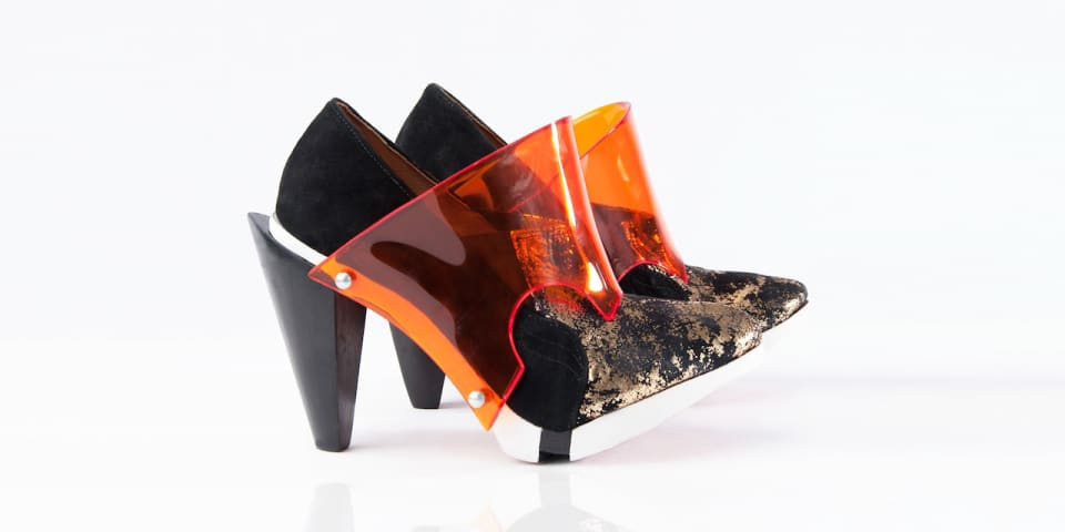 Black and gold geometric heels with a clear orange overlay.
