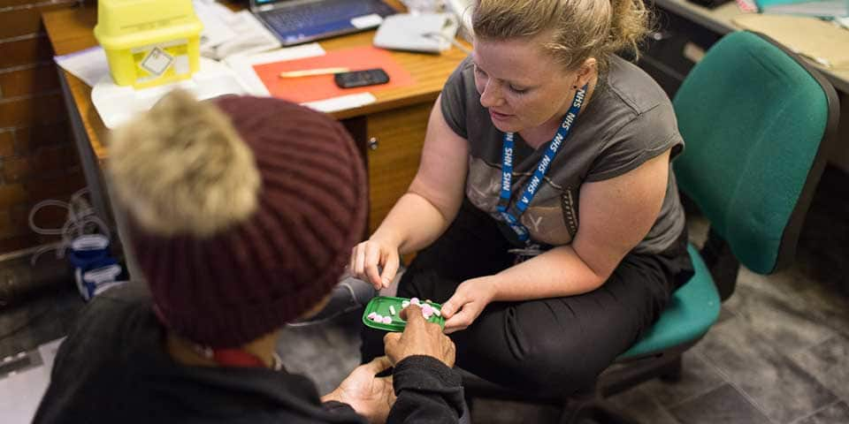 An NHS worker providing medication to a patient