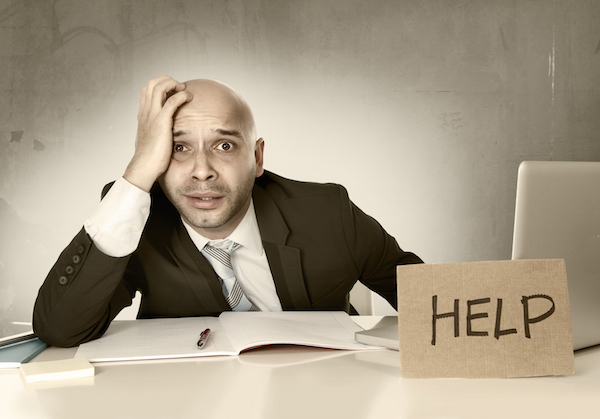 overworked unhappy bald Hispanic businessman in stress wearing suit and tie at office holding help sign working on desk with computer laptop looking frustrated and anxious