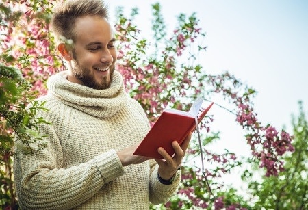 Man with a white tutle neck sweater reading a book next to a bush