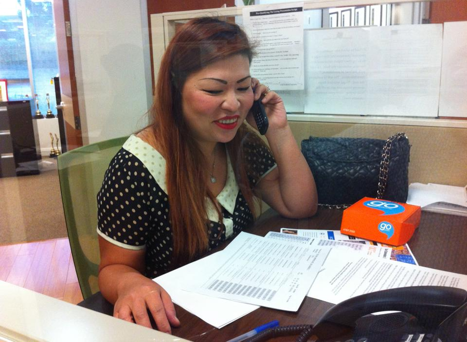 Woman using a disposable AT&T Go Phone at Century 21 Masters telemarketing center in Walnut.