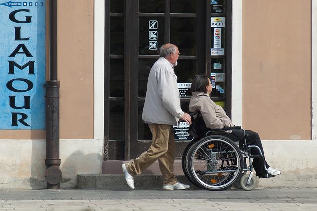 Homem guiando cadeirante na rua.