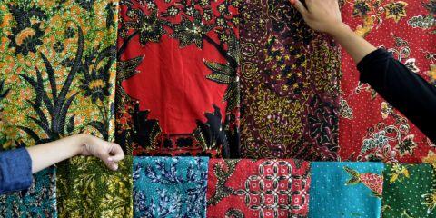 Pekerja menunjukkan kain batik yang siap dipasarkan di sebuah industri rumahan di Kampoeng Batik Jetis, Sidoarjo, Jawa Timur.