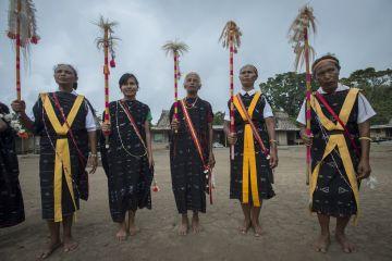 Para penari menggenggam pedang panjang (sau) dan tongkat warna-warni yang pada bagian ujungnya dihiasi dengan bulu kambing berwarna putih (tuba) bersiap mengikuti upacara Reba di Kampung Wogo, Kabupaten Ngada, Pulau Flores, Nusa Tenggara Timur.