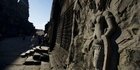 Wisatawan mengamati salah satu bagian candi ketika mengunjungi obyek wisata Angkor Wat di Siem Reap, Kamboja, Minggu (1/12)